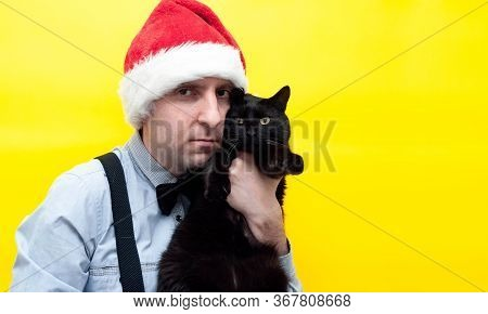 Good-looking Cheerful Man In Red Santa Hat Holding Cute Black Cat Near Cheek And Looking At Camera I