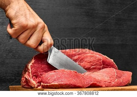 Closeup Man Hand Cutting A Beef Meat With A Knife On A Black Background. Concept Of Healthy Protein