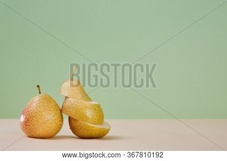 Whole Pear And Divided On Slices. Healthy Nutrition. Summer Mellow Fruit. Diet. Green Background. Co