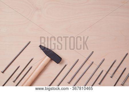 Repairmans Hammer Tool. Big Tacks Placed Diagonally. Repair And Gear Concept. Labor Day. Wooden Back
