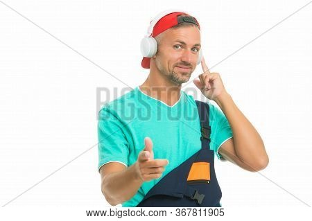 Headphones Protecting Ears. Workman Wear Headphones Pointing Finger. Worker Listen To Music In Headp