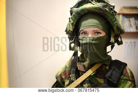 Woman In Military Clothes With Mask Over Light Background And With Vignetting. Female Soldier In Cam