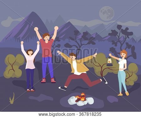 Young Happy People Have Dancing Night Party And Jump Over Bonfire. Male And Female Friends Enjoying