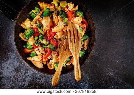 Delicious Healthy Stir Fry Vegetables With Chicken In Pan On Dark Surface.