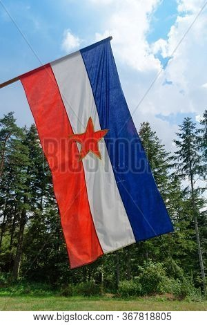 Old Flag Of Former Yugoslavia In A Mountain Forest