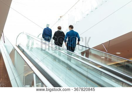 People Standing On The Escalator Steps At A Safe Distance