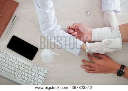 Medical Nurse Wrapping Injured Arm Of Patient With Elastic Bandage, View From Above