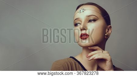 Girl With Dubai Make-up. Perfect Arrows, Red Lips, Gold Jewelry, Jewelry On The Forehead. Indian Gir