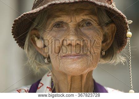 Bangkok, Thailand - April 18, 2011: Thai Senior Woman Using A Hearing Aid. Audiology/medicine/instru