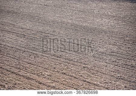 Row In A Plow Field Prepared For Planting Crops In Spring / Plowed Field With Truck In Agricultural