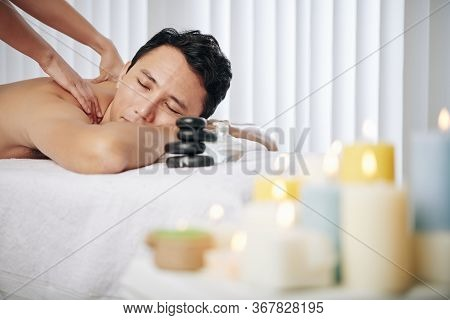 Man Enjoying Relaxing Back And Shoulders Massage In Spa Salon With Burning Scented Candles