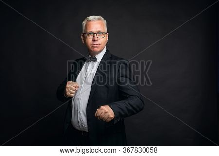 Eccentric Middle-aged Gray-haired Man In A Strict Suit Stands In A Fighting Stance