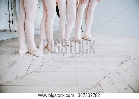 Ballet Dancers Feet On Studio Floor. Teenage Dancer Puts On Ballet Pointe Shoes. Elegance And Balanc