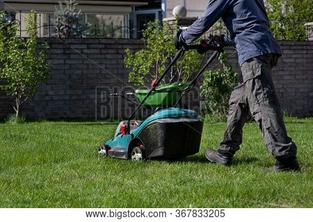 A Man With A Lawn Mower Mows The Grass. Caring For The Backyard. Smooth Beautiful Green Lawn. Garden