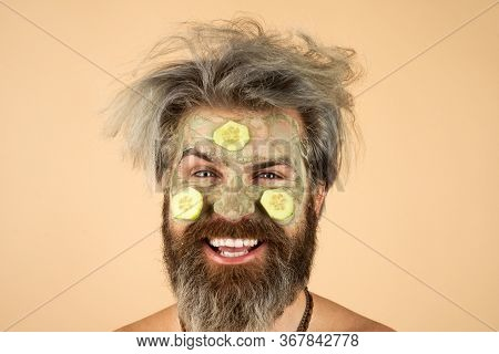 Happy Man With Funny Facial Mask With Cucumber Having Fun. Procedure For Applying Mask From Clay To
