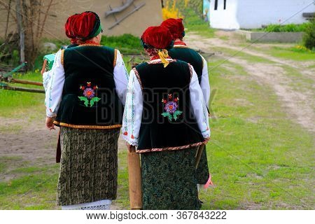 Elderly Women In Ukrainian National Costumes, Embroidered Shirts And Waistcoat Are Walking At Ethnic