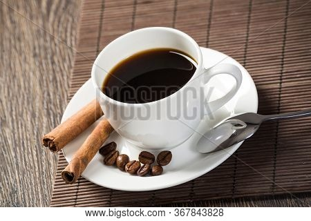 Cup Of Espresso Coffee On Wooden Table With Bamboo Mat. Coffee Beans And Cinnamon Sticks On White Po