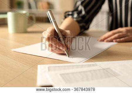 Close Up Of Woman Hands Writing Letter In The Night On A Desk At Home