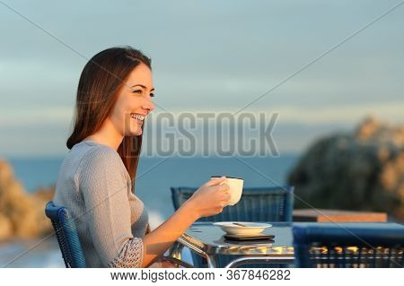Happy Woman Contemplating Sundet Holding Cup In A Coffee Shop On The Beach