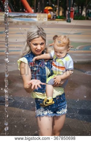 Happy Mother Walks With Her Son In Amusement Park, Cute Woman Holding Her Son In Her Arms