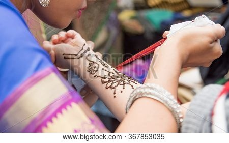 Artists Applying Henna Tattoo On Womens Hands. Mehndi Is Traditional Indian Decorative Art.