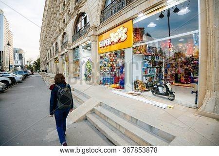 Baku, Azerbaijan - May 2, 2019: Rear View Of Caucasian Woman Walking On Empty Street In Central Baku