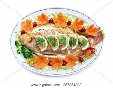 Steamed Fish (tilapia Fish) On Top Lemon Slice With Carved Carrots