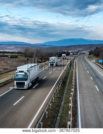 Fleet Of White Trucks In Line As A Convoy At A Rural Countryside Highway Under A Beautiful Blue Sky