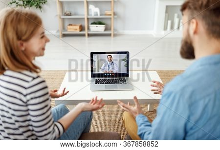 Young Man And Woman Making Notes And Listening To Friendly Psychologist While Making Video Call To C