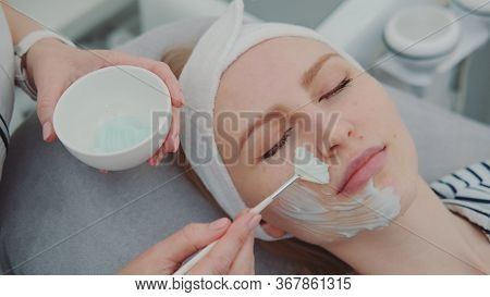 Cosmetician Hands Applying Cream Mask On Young Womans Face At Beauty Spa Salon. Facial Skin Care Tre