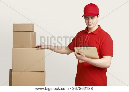 Postman In Uniform At Warehouse Checks For Presence Of All Parcels, Holding Tablet In Hands, Isolate