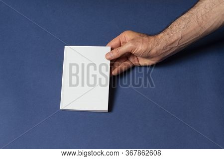 Male Hands Holding A Closed Notebook-catalog With Blank Cover On Blue Background, Mock-up Series Tem