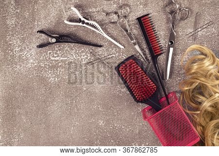 Hairdressing Tools On Light Brown Background. Golden Curls And Pink Combs On Flat Lay, Place For Tex