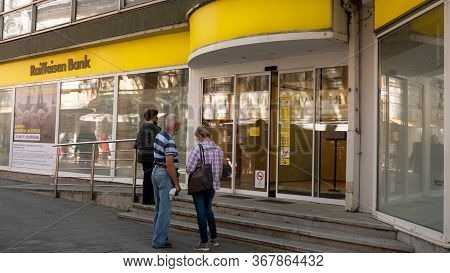 Gyor Hungary 05 22 2020: People In Protective Masks Are Waiting To Get Into A Raiffeisen Bank. The M