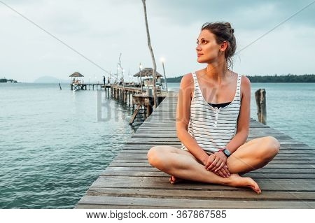 Young Woman Meditating On Pier In Lotus Position At Sunrise