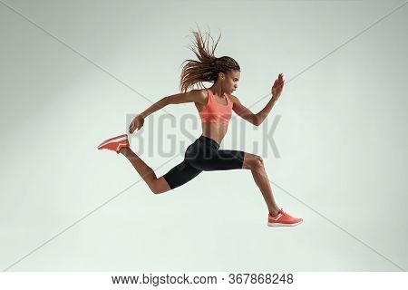 Never Stop Run. Full Length Of Young African Woman With Perfect Body In Sports Clothing Jumping In S