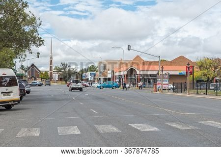 Harrismith, South Africa - March 16, 2020:  A Street Scene, With Businesses, Vehicles, People And A