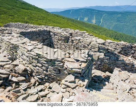 Remnants Of The Old Blindage Of The First World War Laid Out With Stones On The Mountain Slope In Th