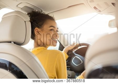Own Car. Cheerful Black Woman Driving Auto Sitting In Drivers Seat In Automobile. Back View, Selecti
