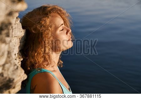 Stylish, Young, Attractive Girl With Closed Eyes Leaning On Rock. Beautiful Lady With Curly Hair Wea