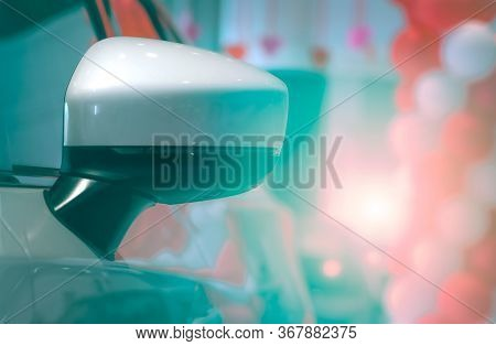Close-up Rear View Wing Mirror Of Luxury Car On Blurred Background Of Modern Showroom Decor With Red