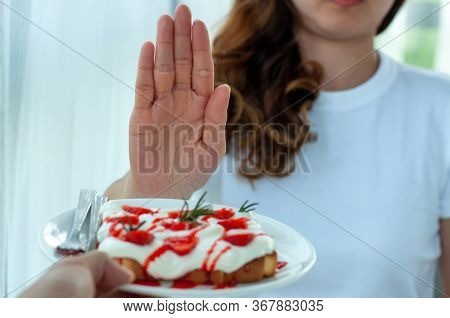 Young Woman Uses The Hand To Push The Plate Of Pastry, Refusing To Eat Flour And Sugar, Intended To