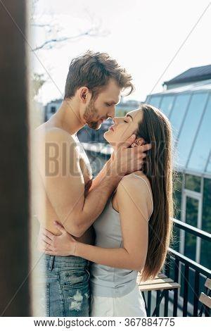 Selective Focus Of Shirtless Man Hugging Girlfriend On Balcony