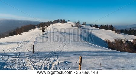 Cienkow Nizni Hill With Snow Covered Road, Meadows And Trees Above Wisla Resort In Winter Beskid Sla
