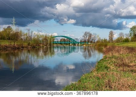 Olse River With Railway Bridge Over In Karvina City In Czech Republic During Springtime Day With Blu