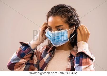 Studio Shot Portrait Of Beautiful African-american Ethnicity Woman Who Is Putting Protective Mask.