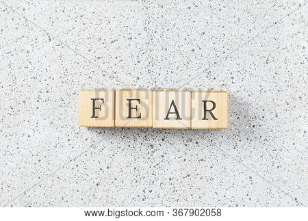 Fear Word Made With Wooden Building Blocks On Grey Cork Background. Uncertainty And Panic Concept