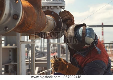 Welder In The Mask And Protective Clothing Is Gaining Increased Cladding Weld