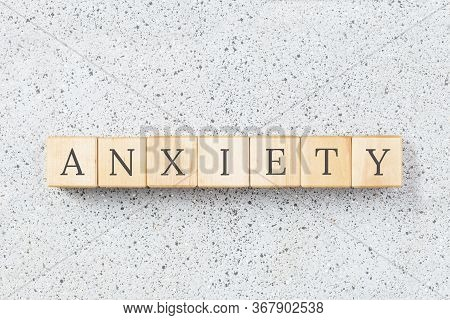 Anxiety Word Made With Wooden Buildning Blocks On Grey Cork Background. Uncertainty And Panic Concep