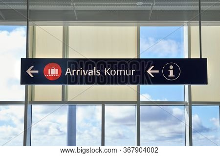 Arrivals sign at an airport in English and Icelandic. Komur translates to arrivals.